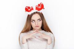 美丽的情感白肤金发的女性式样穿戴圣诞老人鹿戴头受话器 背景圣诞节概念问候查出白色 免版税图库摄影