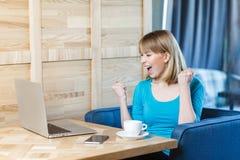 美丽的惊奇满意的正面少女自由职业者画象有金发的在蓝色T恤杉在咖啡馆坐和 免版税库存照片