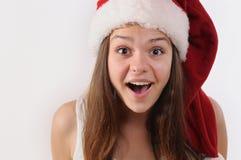 美丽的惊奇的女孩画象圣诞老人帽子的 库存图片