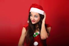 美丽的想法的做鬼脸的妇女在圣诞老人圣诞节费用 库存照片