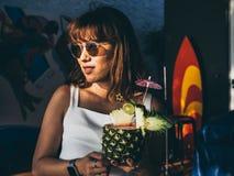 美丽的愉快的亚裔拿着菠萝汁鸡尾酒的妇女佩带白色无袖的和太阳镜在夏天 图库摄影