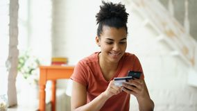 美丽的愉快的使用在家在网上购物与信用卡生活方式的智能手机的混合的族种妇女网路银行 库存照片