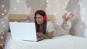 美丽的愉快的女孩在一张大床上说谎使用一台白色计算机移动计算机并且听到在耳机的音乐 股票录像