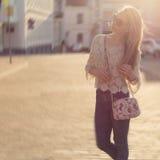 美丽的愉快的女孩柔和的步行通过城市nazakate太阳镜,太阳房间柔和定调子 库存图片