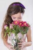 美丽的愉快的女孩给一朵野生兰花 免版税库存照片