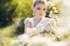 美丽的愉快的妇女在一个用花装饰的春天庭院里 图库摄影