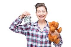 美丽的愉快的妇女在上床前显示一个闹钟 库存图片