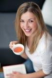 美丽的愉快的妇女饮用的茶 库存图片