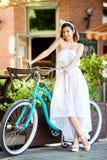 美丽的愉快的妇女骑马自行车在城市 免版税库存照片