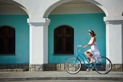 美丽的愉快的妇女骑马自行车在城市 库存照片