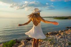 美丽的愉快的少妇在白色夏天缎礼服a的后面 免版税库存照片