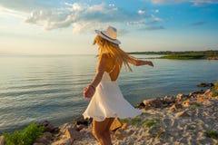 美丽的愉快的少妇在白色夏天缎礼服a的后面 免版税库存图片