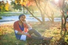 美丽的愉快的少妇在秋天公园 快乐的妇女在一个巧妙的电话谈话户外以明亮的黄色 库存图片