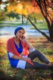 美丽的愉快的少妇在秋天公园 快乐的妇女在一个巧妙的电话谈话户外以明亮的黄色 免版税库存照片