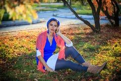 美丽的愉快的少妇在秋天公园 快乐的妇女在一个巧妙的电话谈话户外以明亮的黄色 库存照片