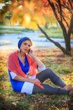 美丽的愉快的少妇在秋天公园 快乐的妇女在一个巧妙的电话谈话户外以明亮的黄色 免版税库存图片