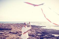 美丽的愉快的少妇女孩发射风筝在海滨 免版税图库摄影