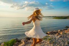 美丽的愉快的少妇白色夏天缎礼服的和a的 图库摄影