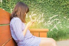 美丽的愉快的微笑和手机短信的坐公园长椅的混合的族种亚裔女孩少年女性少妇 免版税库存照片