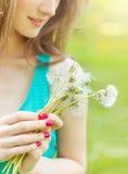 美丽的愉快的微笑的女孩用长的蒲公英在短裤和T恤杉的手上在公园休息在一个晴天 库存图片