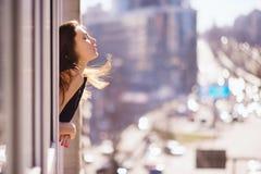 年轻美丽的愉快的微笑的妇女照片有长的头发的在窗口附近 晴朗的日 背景秀丽城市生活方式都市妇女年轻人 免版税库存照片