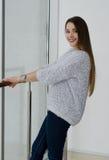 年轻美丽的愉快的微笑的妇女照片有长的头发的在窗口附近 免版税库存照片