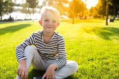 美丽的愉快的微笑的小男孩坐看照相机的草 免版税库存照片