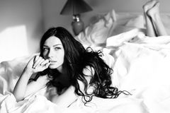 美丽的愉快的微笑的少妇的黑白图象在查寻的床上 库存照片