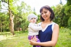 美丽的愉快的微笑的母亲画象有室外的婴孩的 免版税库存照片