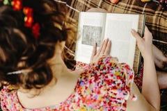 美丽的愉快的新娘和时髦的减速火箭的新郎,阅读书和 库存图片