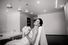美丽的愉快的新娘画象坐沙发 免版税库存照片
