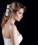 美丽的愉快的柔和的妇女新娘画象一根白色婚礼礼服c美丽的沙龙婚礼头发的有在她的白花的 图库摄影