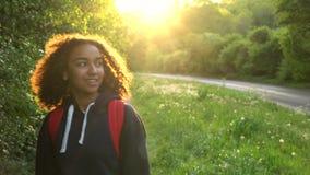 美丽的愉快的步行与红色背包的混合的族种非裔美国人的女孩少年女性少妇在国家在日落 股票录像