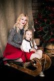 美丽的愉快的母亲和女儿有圣诞节冬天雪橇的在新年的装饰内部与欢乐Christm 免版税图库摄影