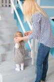 年轻美丽的愉快的母亲帮助她的做她的第一步的女儿 库存图片