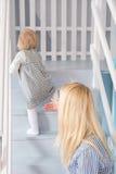 年轻美丽的愉快的母亲帮助她的做她的第一步的女儿 免版税库存照片