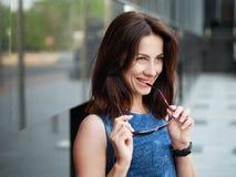美丽的成人红头发人妇女的关闭蓝色牛仔裤的穿戴摆在街道 免版税库存照片