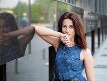 美丽的成人红头发人妇女的关闭蓝色牛仔裤的穿戴摆在街道 库存照片
