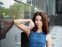 美丽的成人红头发人妇女的关闭蓝色牛仔裤的穿戴摆在街道 图库摄影