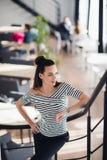 去美丽的成功的深色的妇女画象站立在她的咖啡馆和在楼上,当看时 库存图片