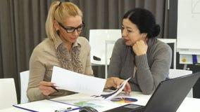 美丽的成熟妇女和她的资深企业colelague在会议 库存照片