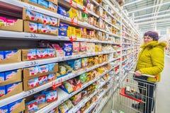 美丽的成熟妇女在一个大购物中心选择不同的好吃的东西 免版税库存照片