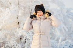 美丽的成熟妇女在夹克下的白色冬天在冬天投入敞篷 免版税库存照片