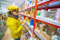 美丽的成熟妇女选择在一个小店的洗涤剂 免版税库存图片