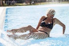 美丽的成熟妇女,当喷洒水时 免版税库存图片