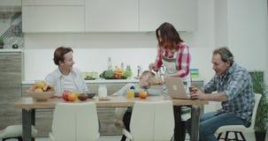 美丽的成熟家庭早晨吃早餐在愉快大桌的母亲一起准备板材与 影视素材