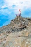美丽的成熟年迈的妇女坐在做瑜伽的峭壁顶部 免版税库存图片