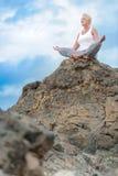 美丽的成熟年迈的妇女坐在做瑜伽的峭壁顶部 库存图片