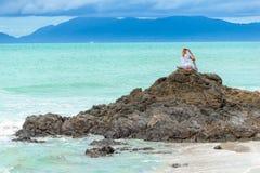 美丽的成熟年迈的妇女坐在做瑜伽的峭壁顶部 免版税库存照片