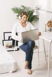 美丽的成熟的商业妇女与膝上型计算机一起使用在家。 库存图片